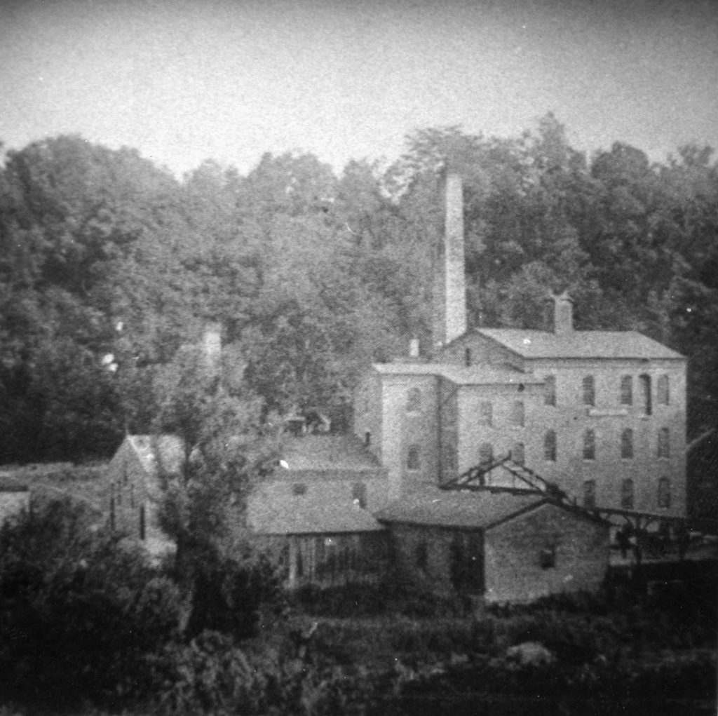 Grainy image of original Mudlick Distillery from the late-1800s, showcasing our history